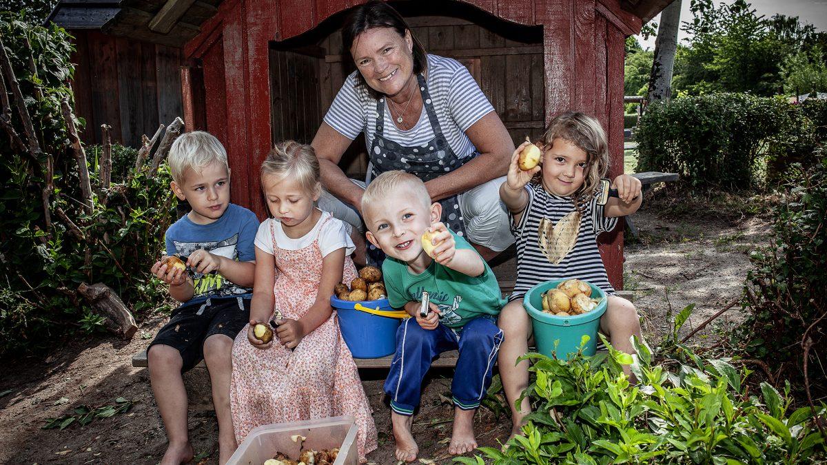 Billede fra maddag 2019 med køkkenfaglig medarbejder og glade børn.