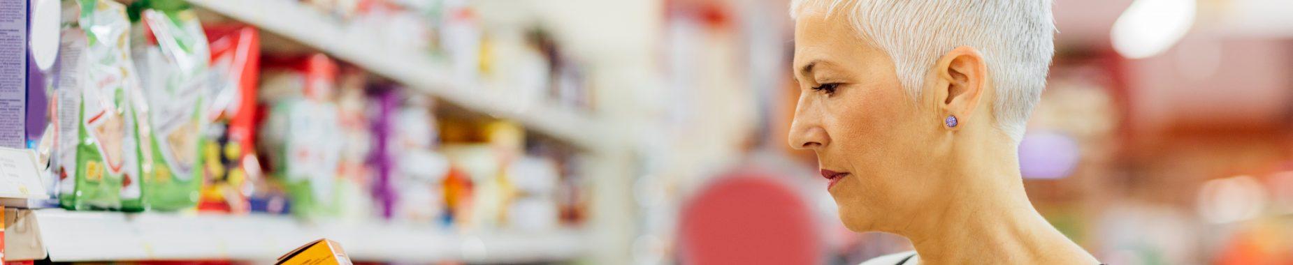 Kvinde kigger på vareindholdet på en fødevarer for at tjekke hvad der er sunde fødevarer til mennesker med diabetes