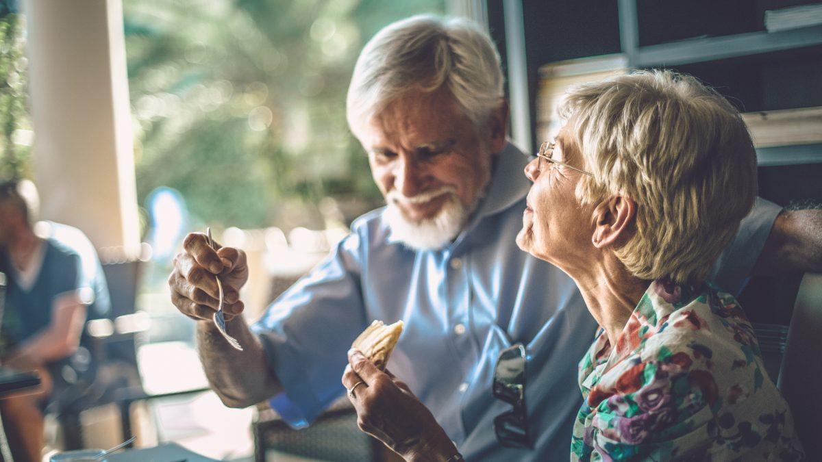 To ældre sidder og nyder mad